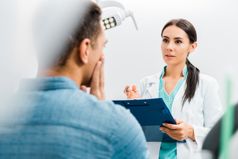 Dentist talking to patient during dental checkup