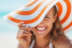Woman in sun hat smiles without gum disease
