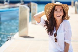 Woman in sunhat and beautiful smile from cosmetic dentistry